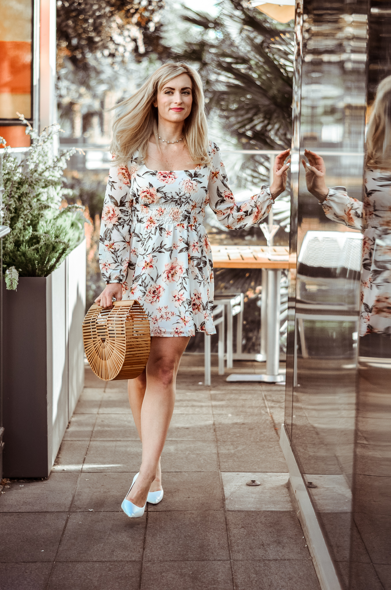 blonde wearing a floral long sleeve mini dress with white heels