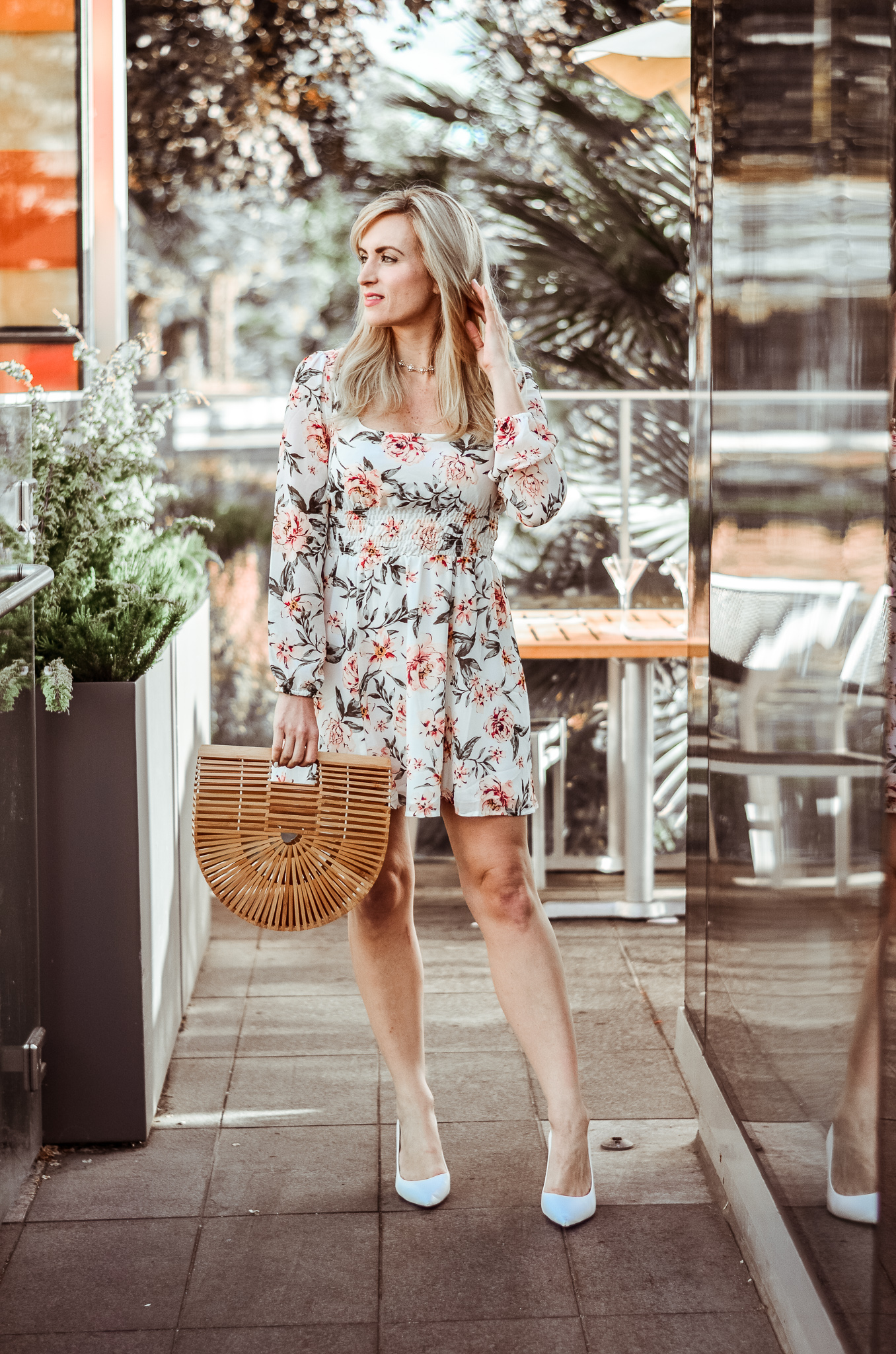 blonde blogger legallee blonde wearing a floral long sleeve mini dress and a bamboo handbag