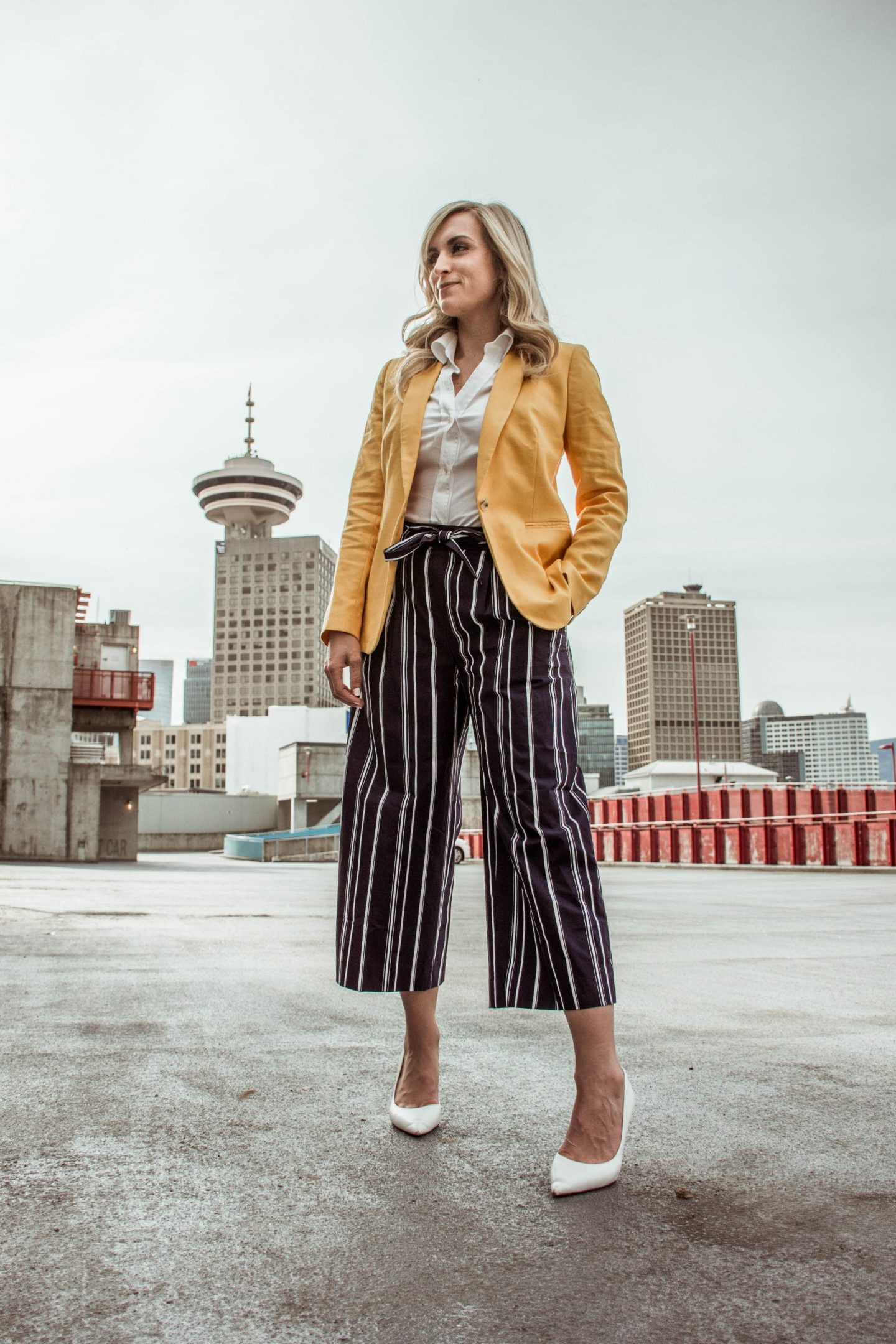 legallee blonde fashion blogger wearing yellow blazer and striped culotte pants