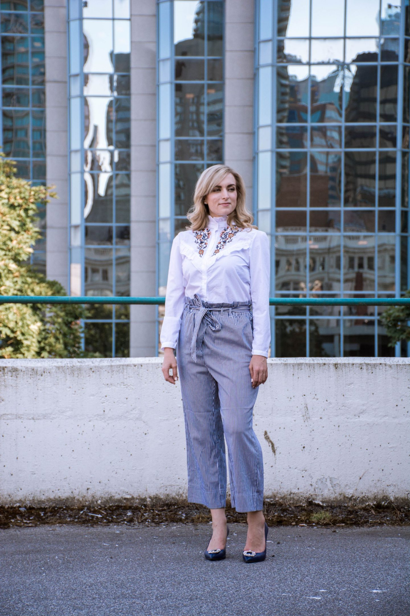 fashion blogger wearing embroidered ruffle collar shirt and striped tie waist pants