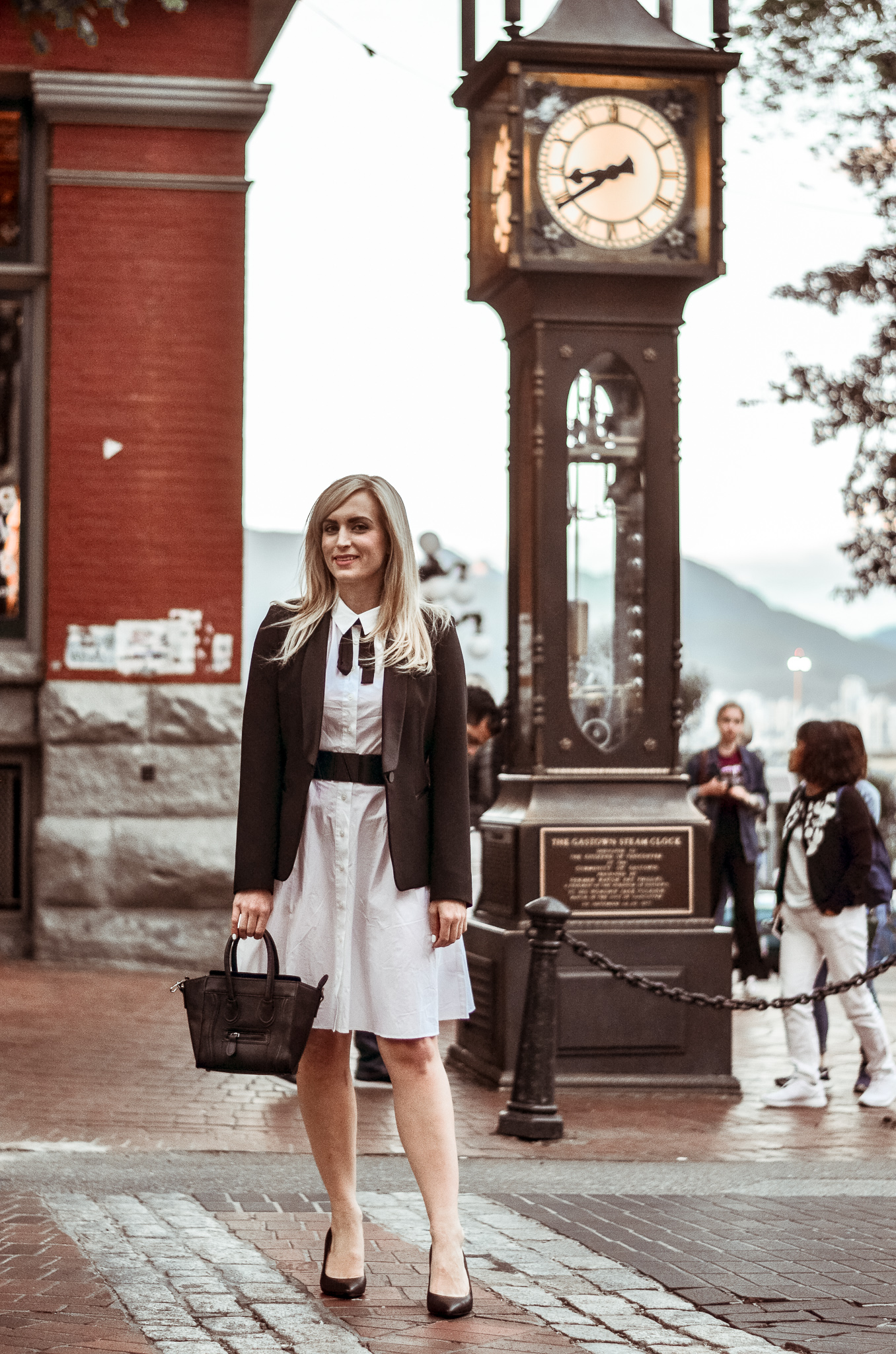 legallee blonde fashion blogger standing by Vancouver Gastown steam clock in white dress with black blazer