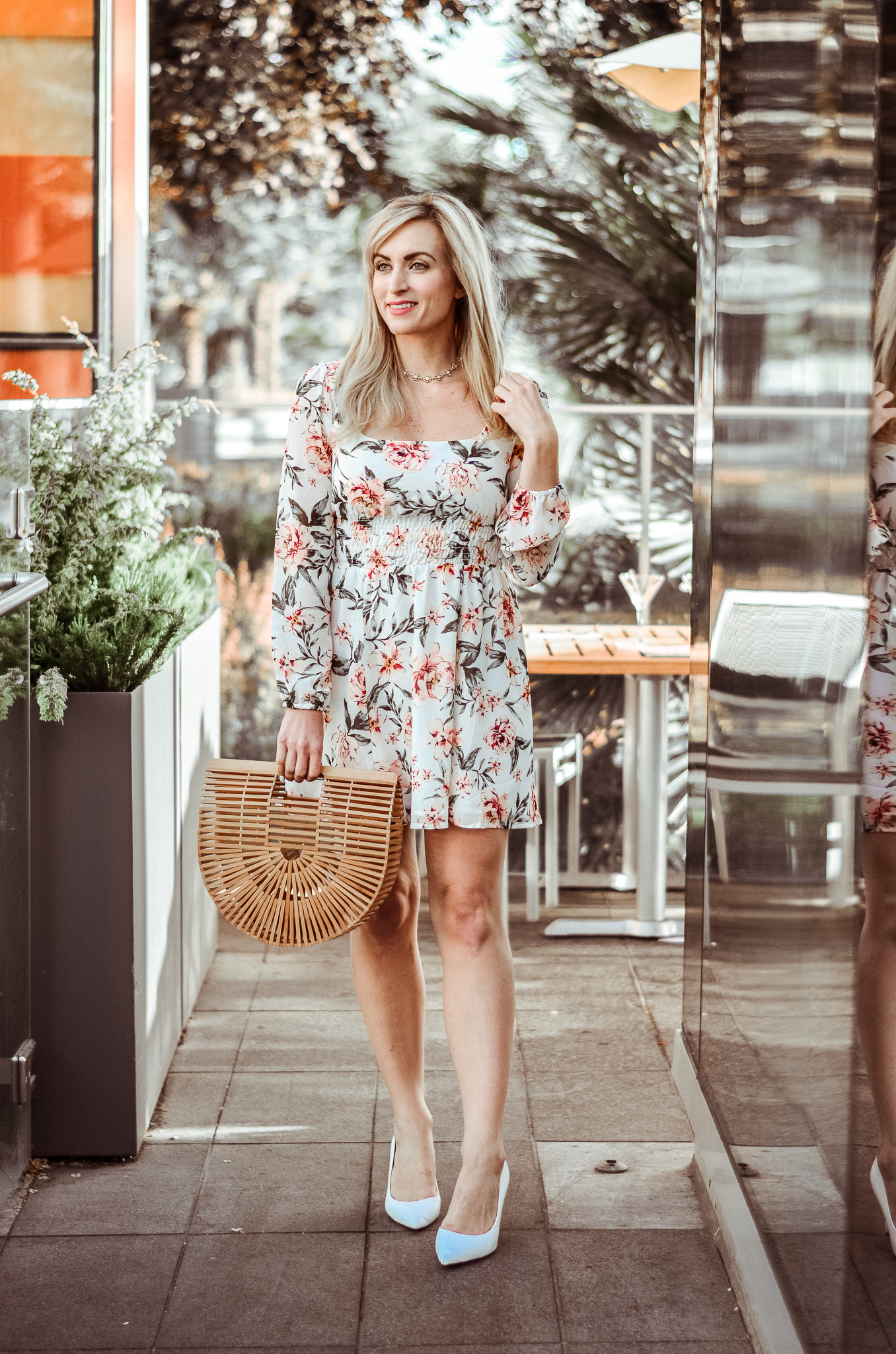 blonde wearing long sleeve white floral dress with bamboo handbag and white high heels