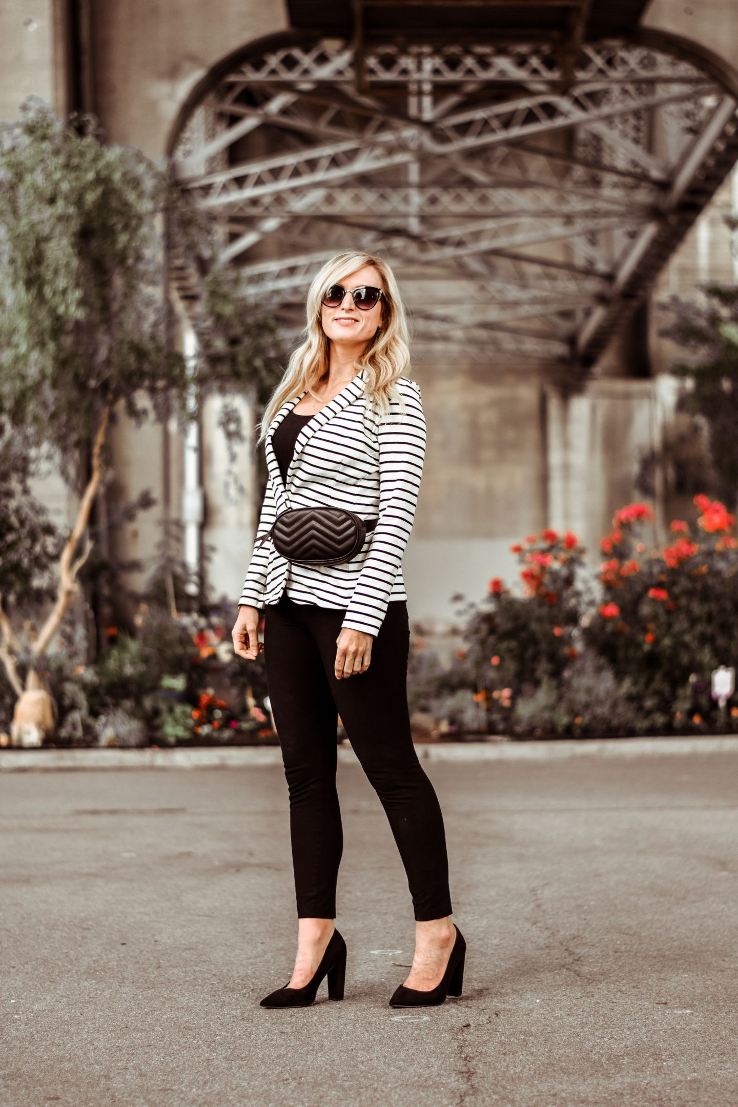 blonde wearing striped blazer black fanny pack showing what to wear with a striped blazer