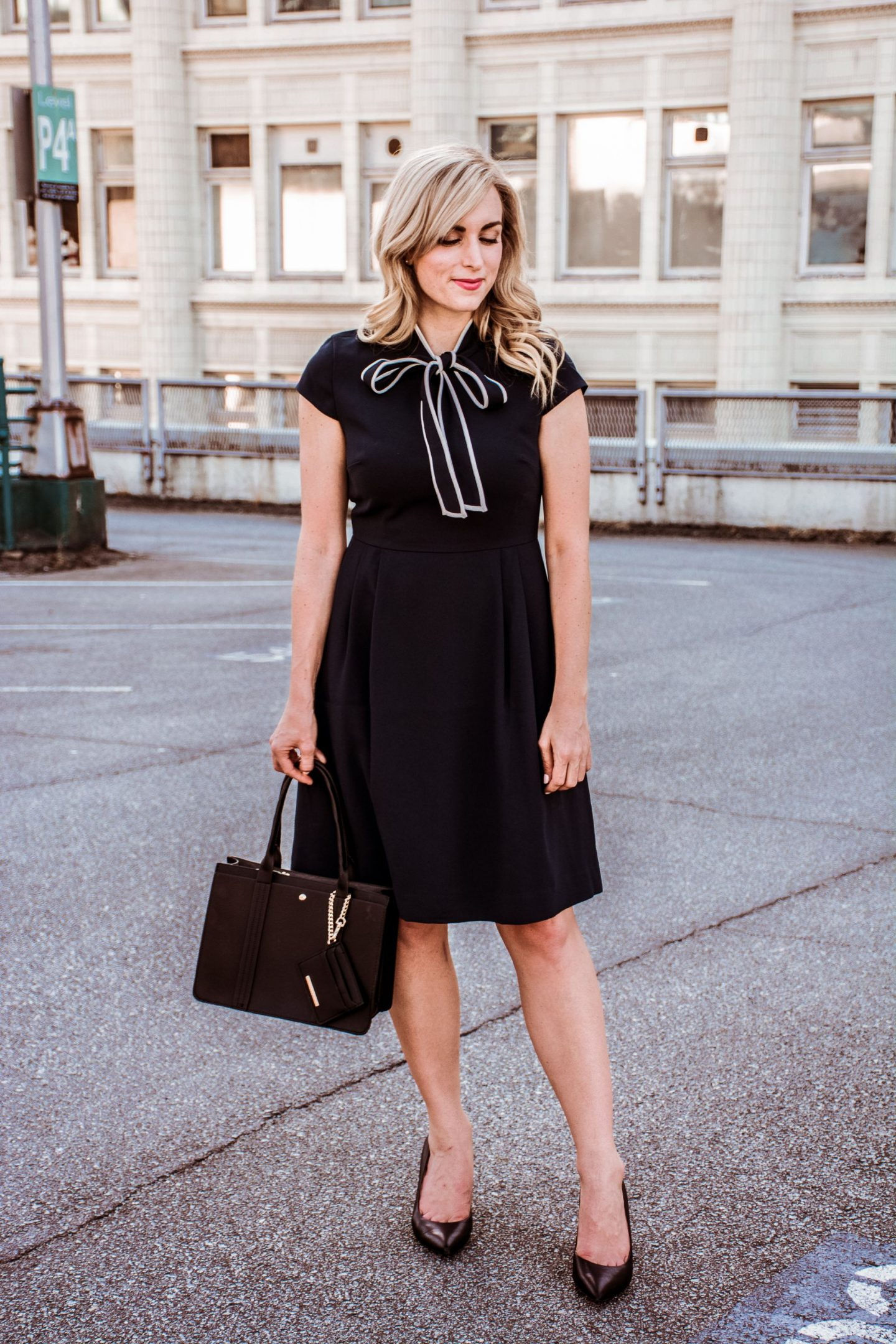 outfit idea navy tie-neck dress with black handbag