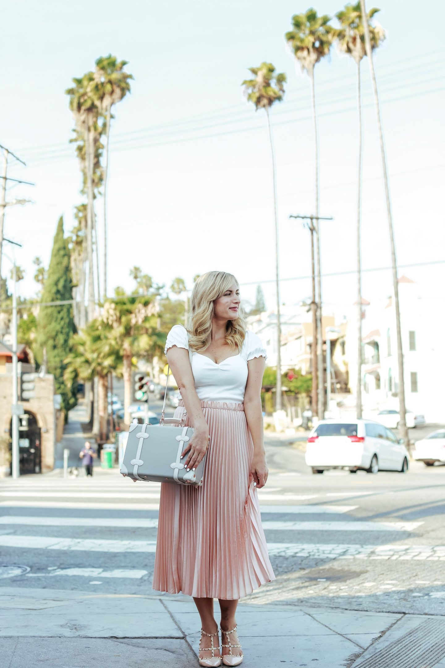 pink pleated midi skirt with vintage inspired luggage and white crop top