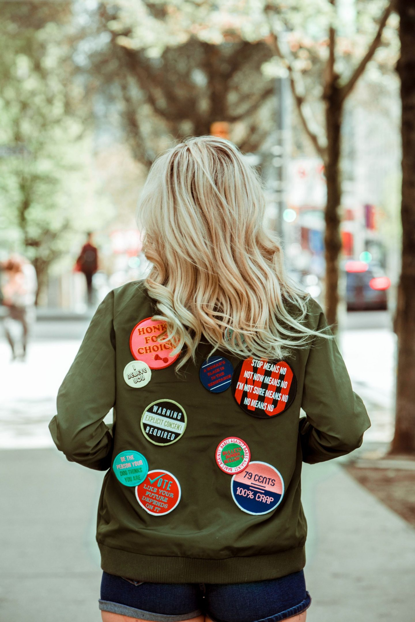 intersectional feminism - blonde wearing feminist patch bomber jacket
