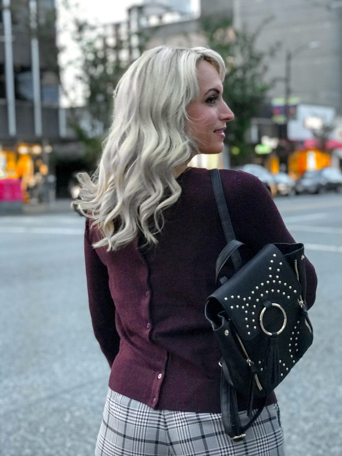 button cardigan worn backwards with studded back pack