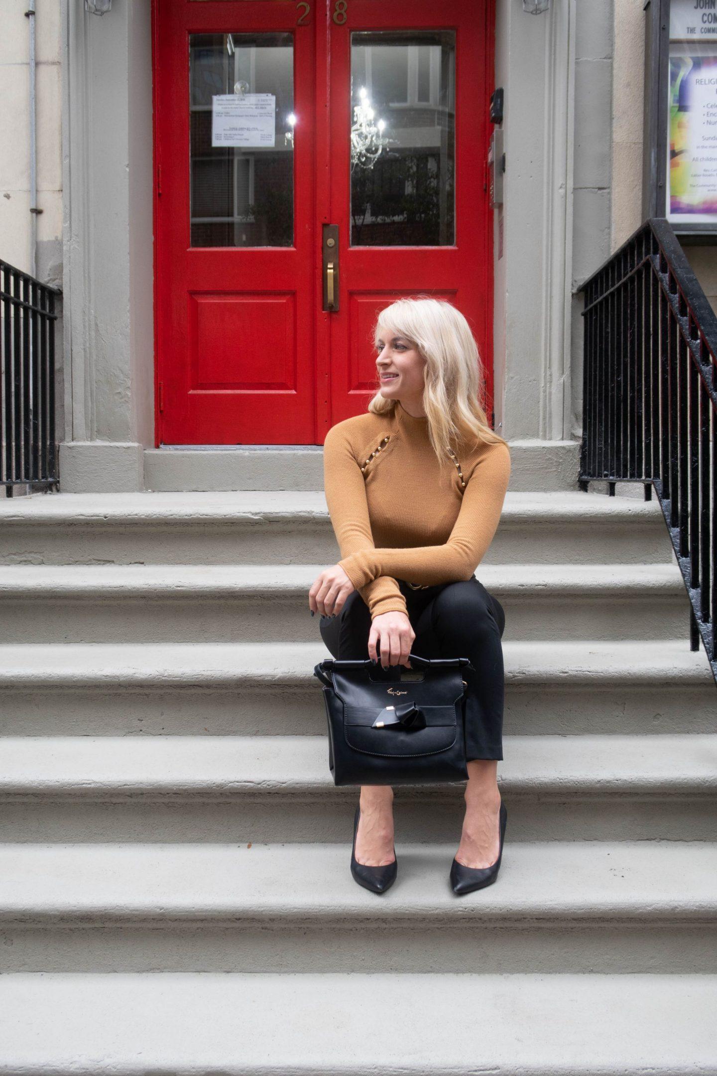 legallee blonde sitting holding a foley & corinna handbag