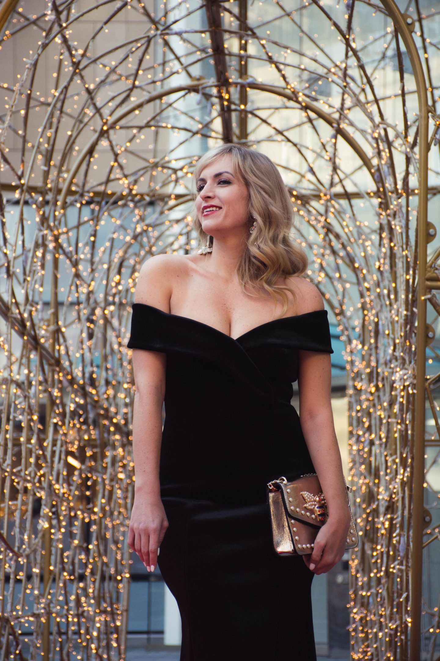 legallee blonde wearing an off the shoulder black velvet gown. what to wear to a black tie holiday party