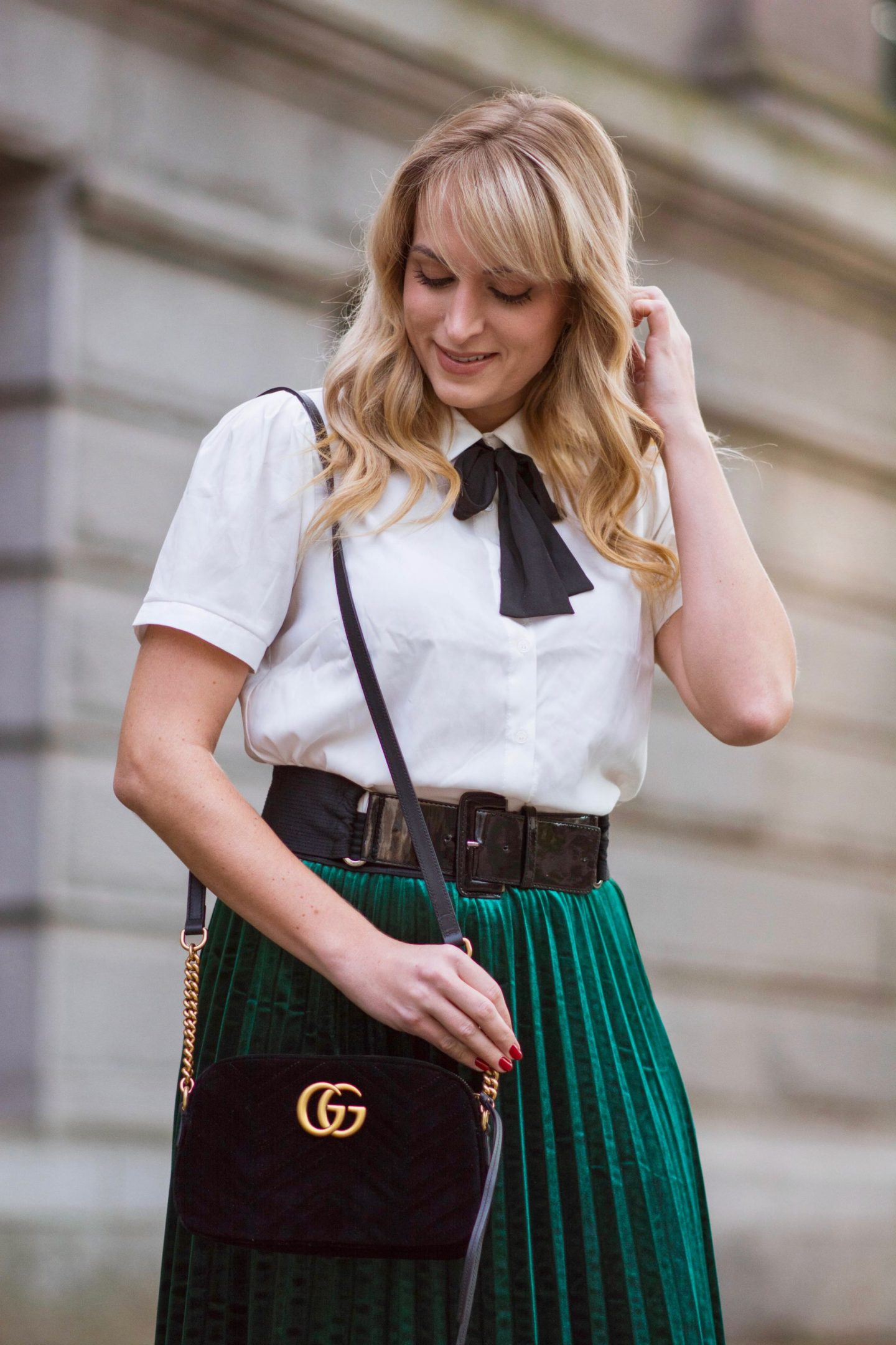 blonde-wearing-blouse-green-pleated-skirt-gucci-bag