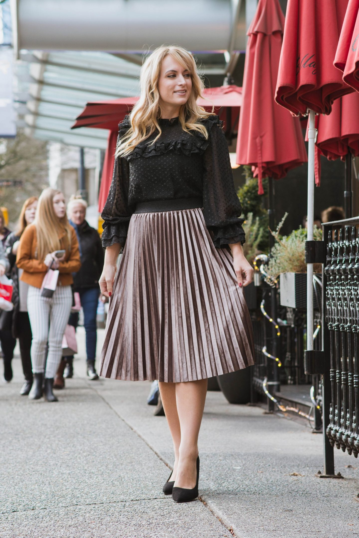 one-woman-wearing-pleated-velvet-midi-skirt-and-black-blouse