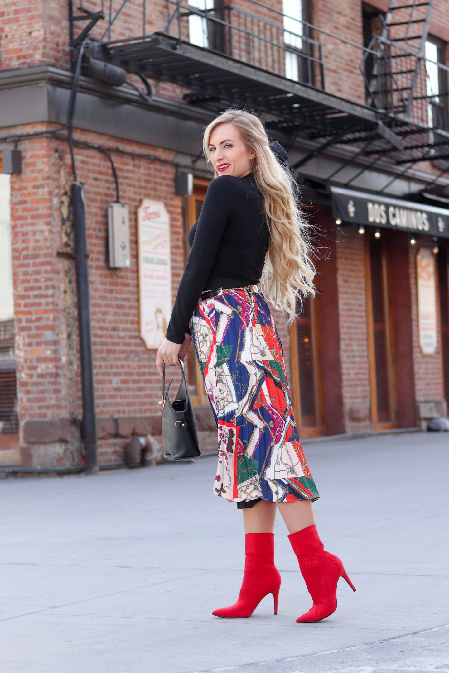 blonde standing wearing a scarf print midi skirt and red ankle boots