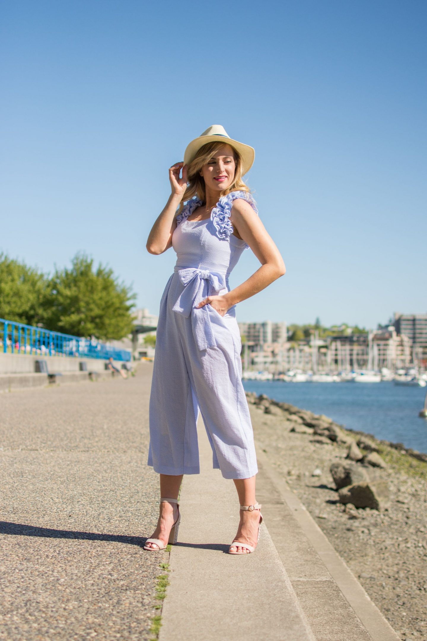 woman standing by ocean wearing seersucker jumpsuit by eliza j and straw fedora