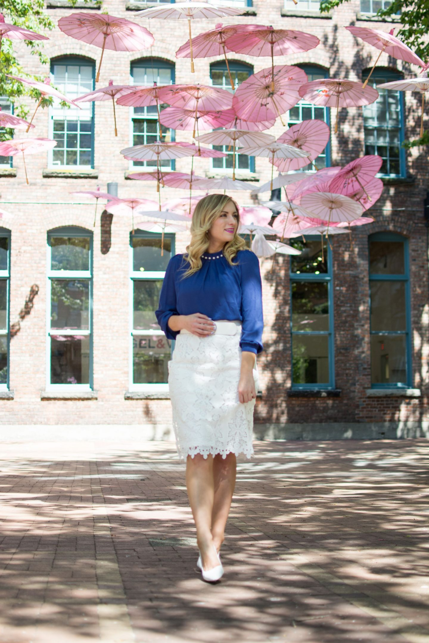 woman standing in white lace pencil skirt and blue top. outfit for how to style lace for the office