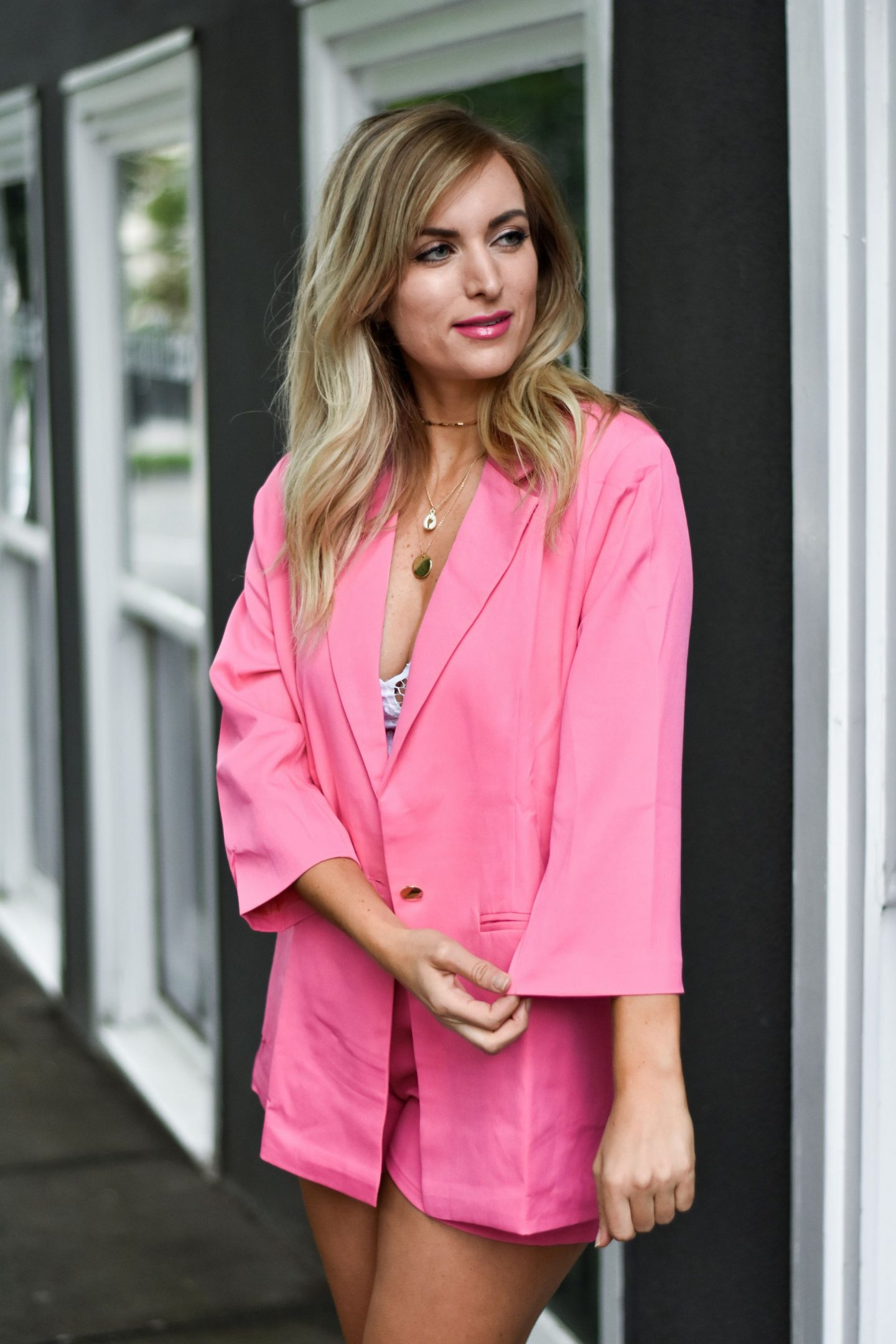 woman wearing a pink blazer and matching shorts set