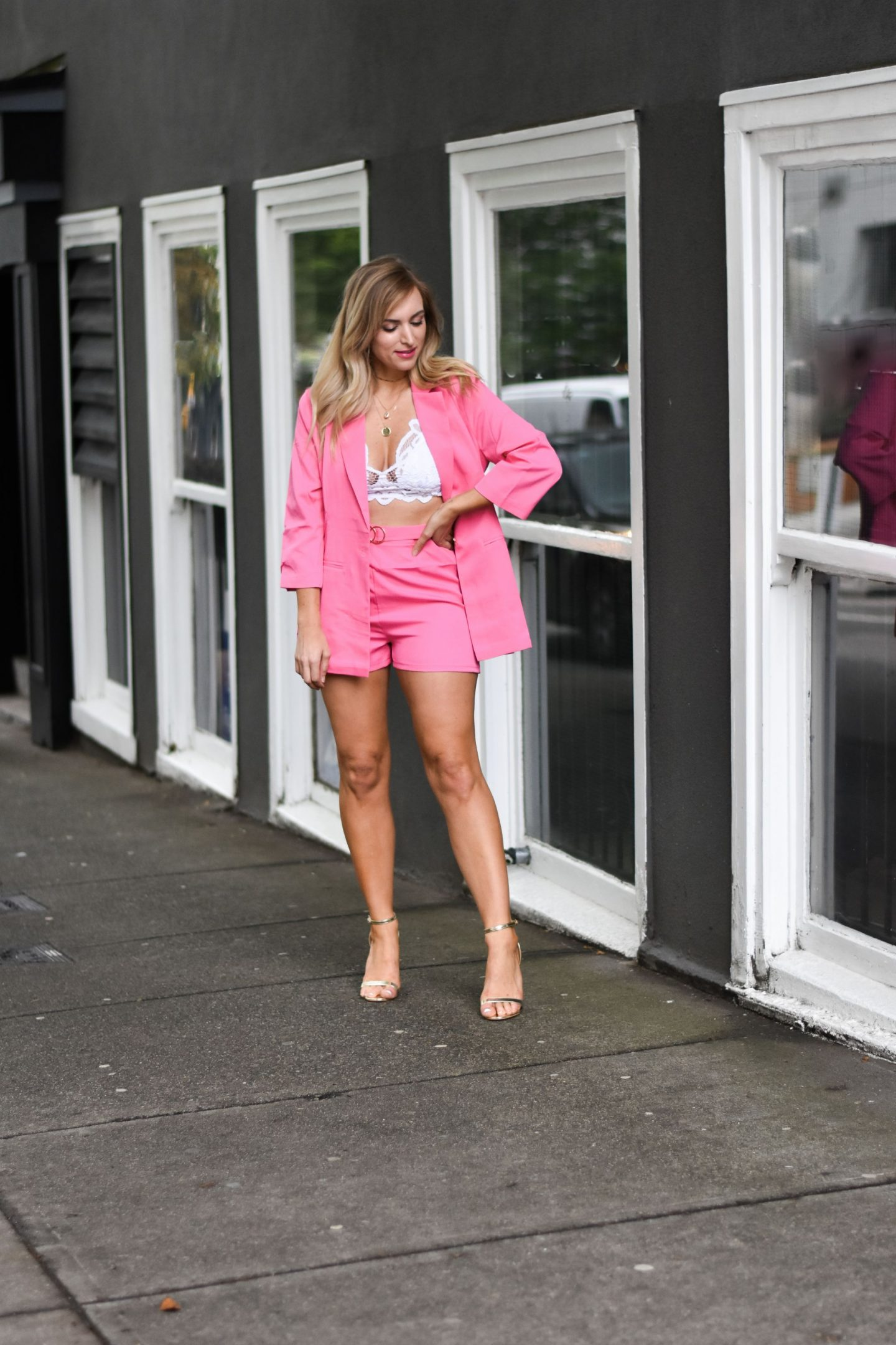 one woman wearing a pink blazer and shorts set summer fashion trend