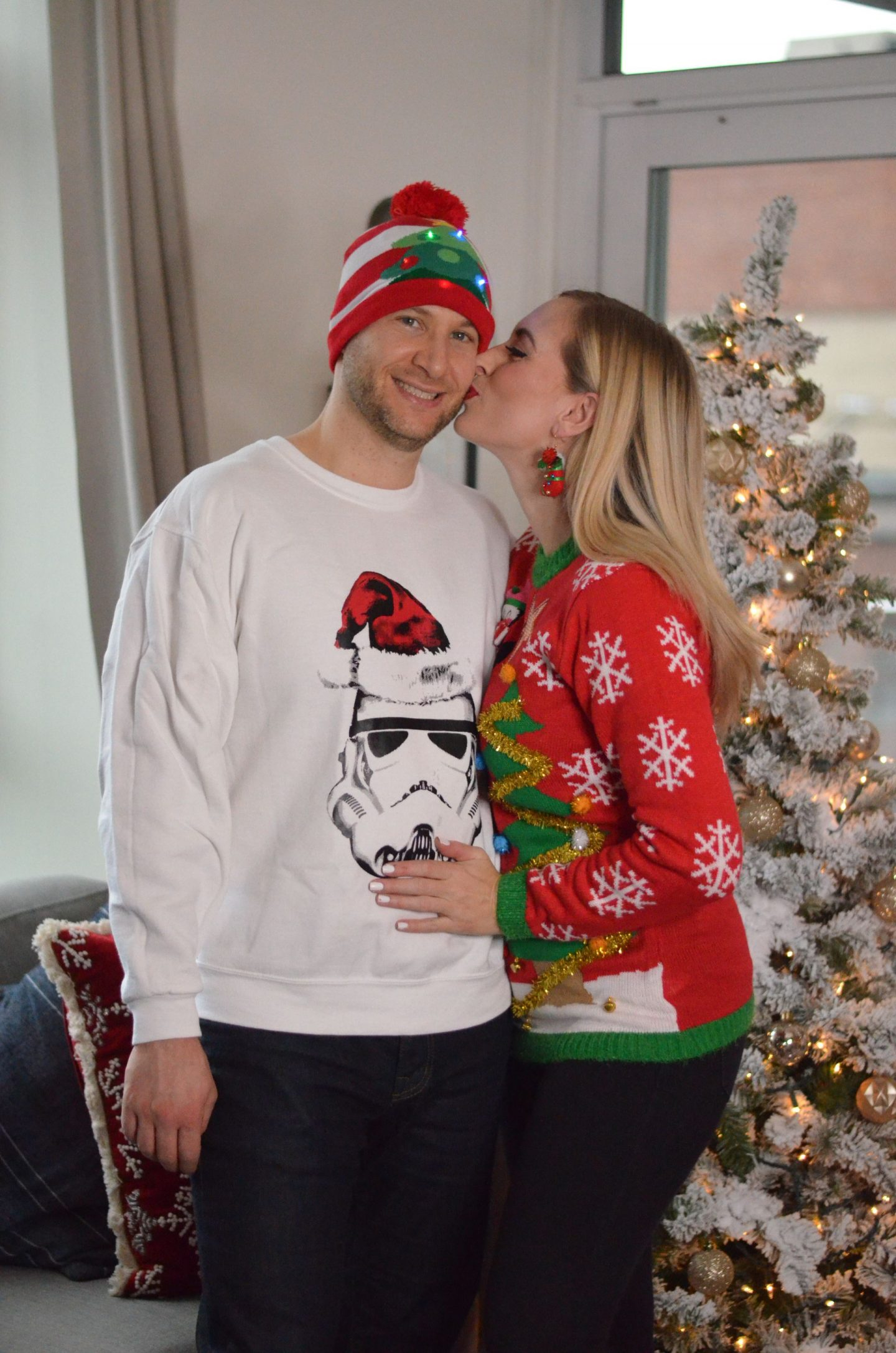 two people by a christmas tree in ugly christmas sweaters