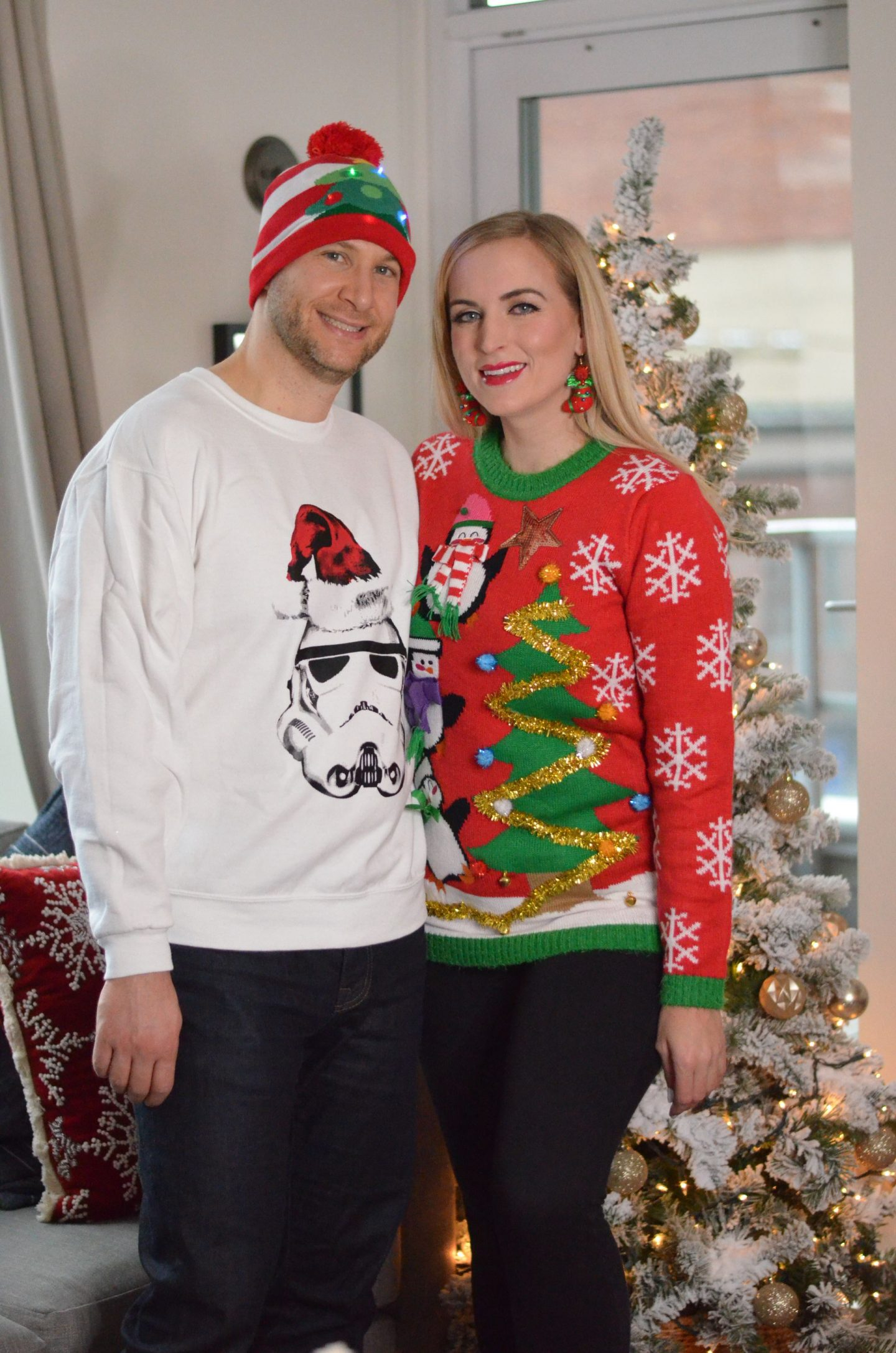 man and woman standing wearing ugly christmas sweaters for an ugly christmas sweater party