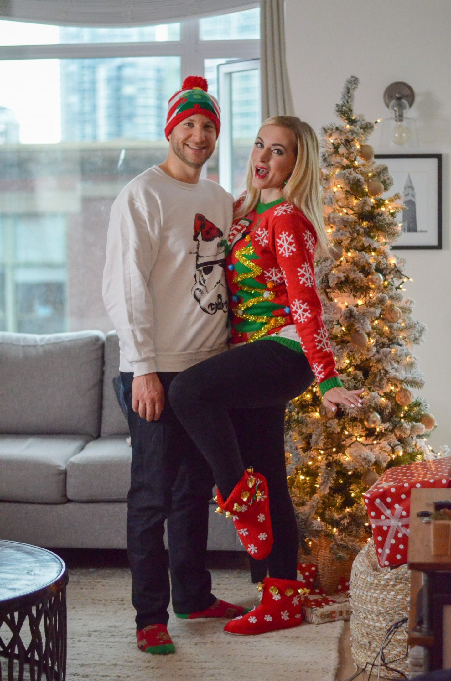 man and woman standing beside a christmas tree wearing ugly christmas sweaters
