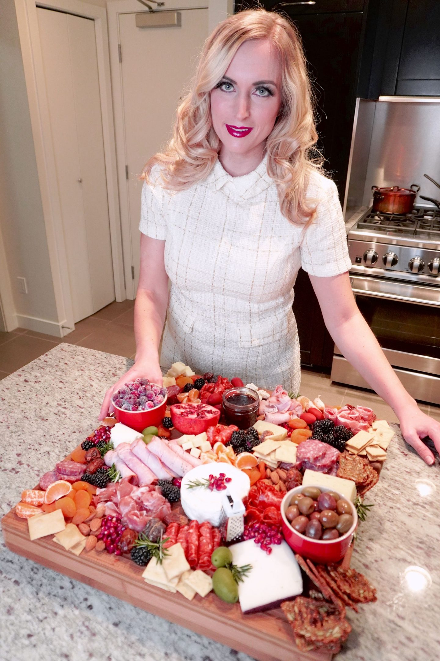 one woman in kitchen with a charcuterie board