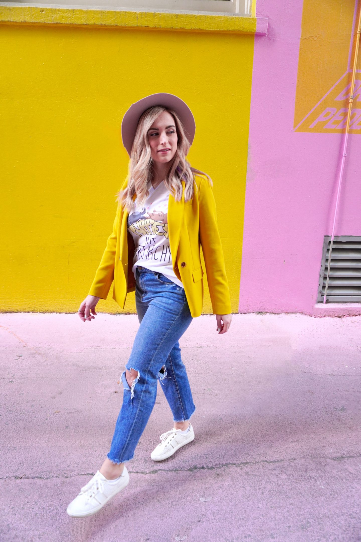 woman wearing yellow blazer and graphic tee inspired by Jane Fonda