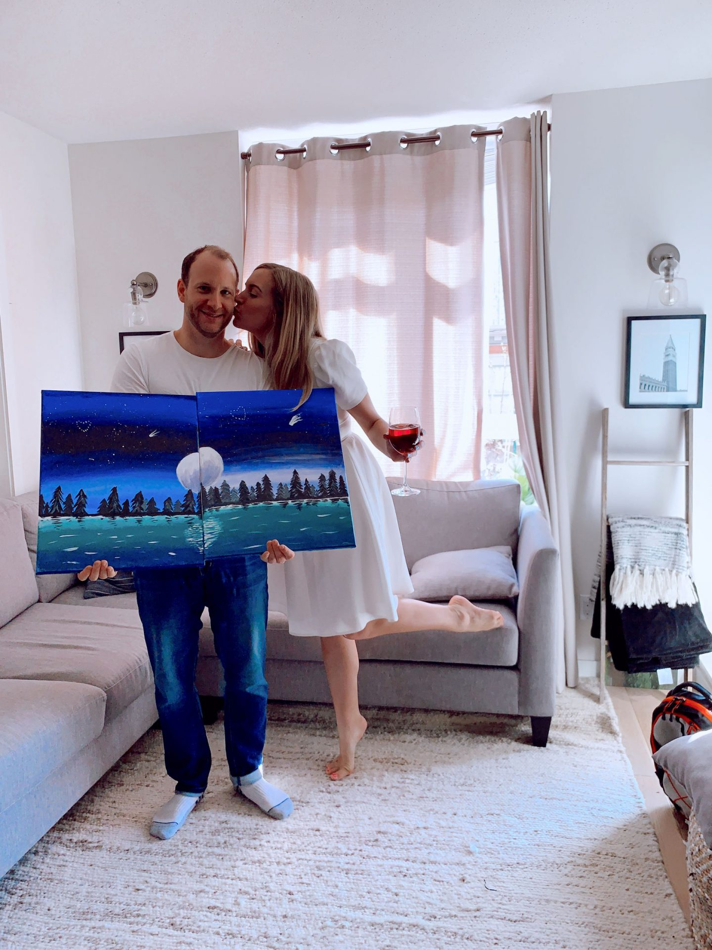couple holding a painting at-home date night ideas