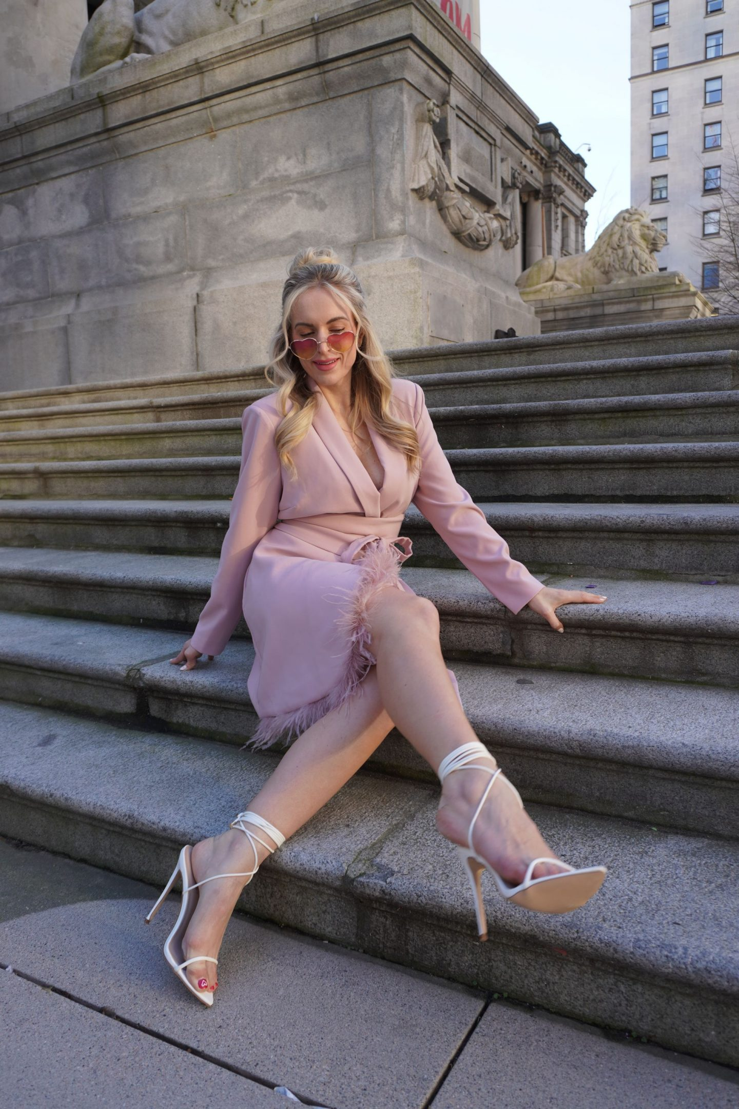 legallee blonde fashion blogger sitting on steps wearing a pink feather blazer dress