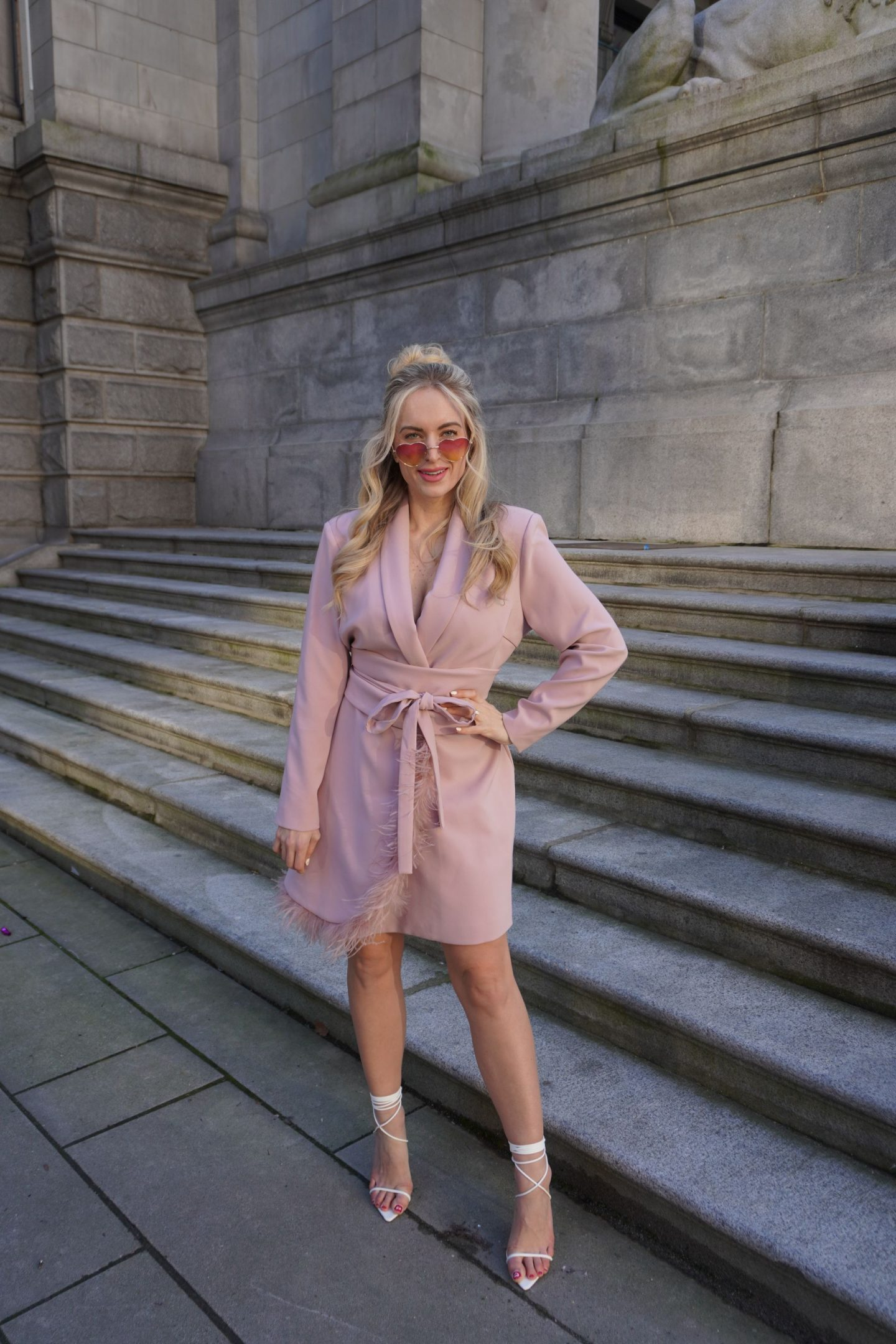 fashion blogger legallee blonde standing wear one of spring's fashion trends - feathers - in a pink blazer dress with feathers
