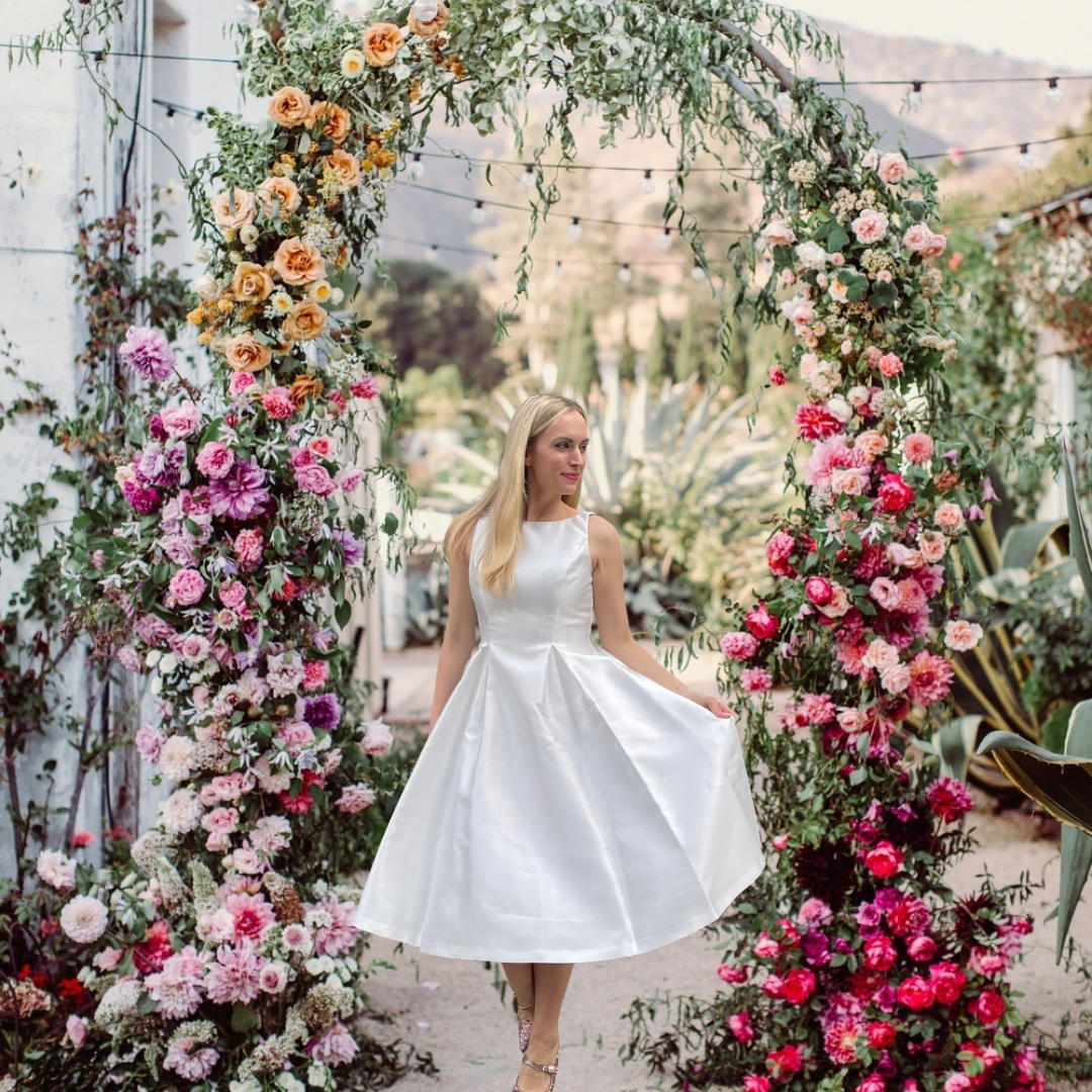 fashion blogger legallee blonde on how she makes money blogging. Image is woman in white dress standing under a floral archway