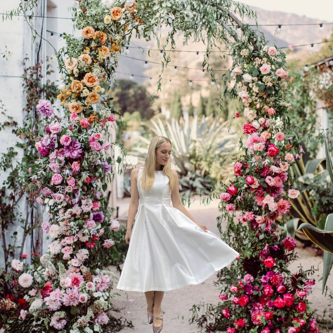 fashion blogger legallee blonde wearing a white dress under a floral archway