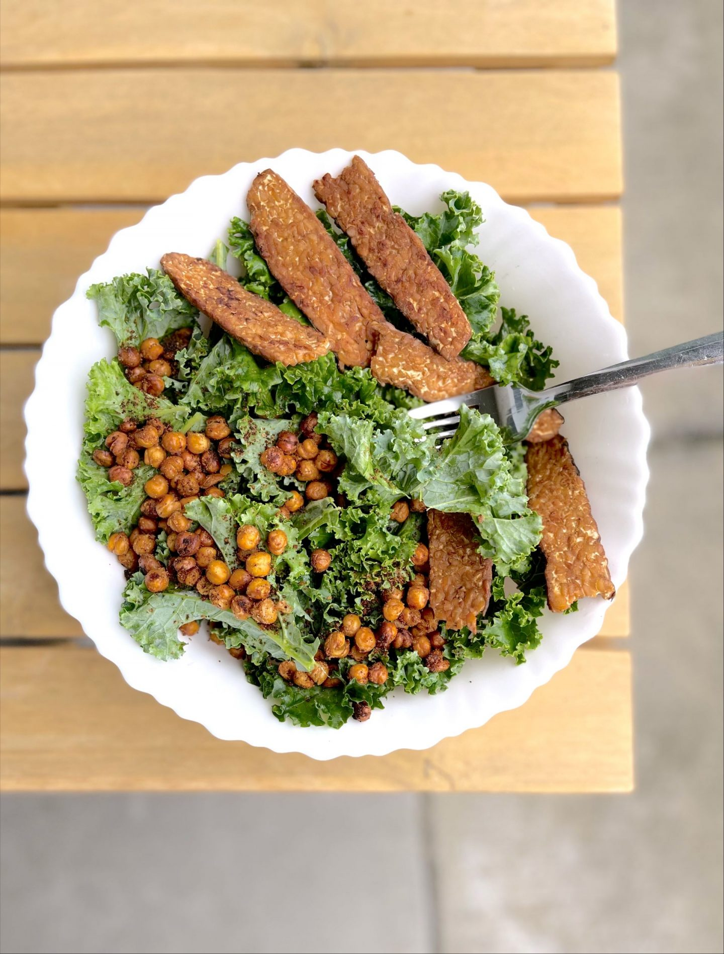 kale tempeh and roasted chickpea salad in a white bowl on a wooden table