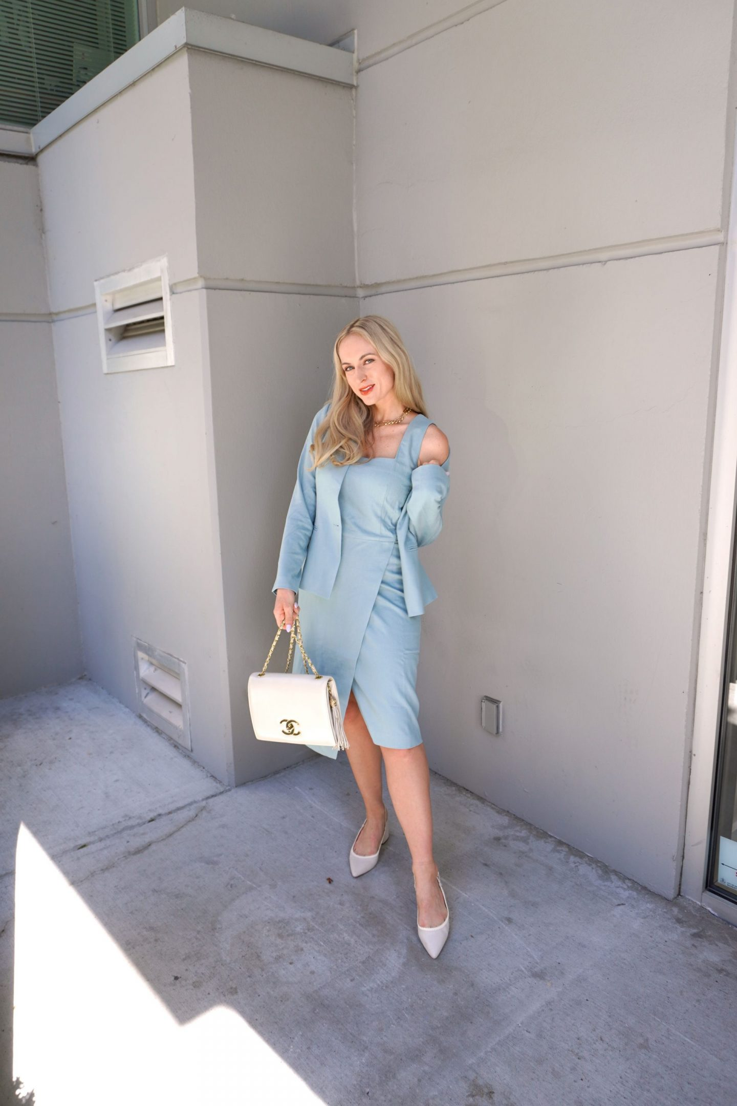 blonde woman standing in a teal dress and blazer - summer work wear outfit