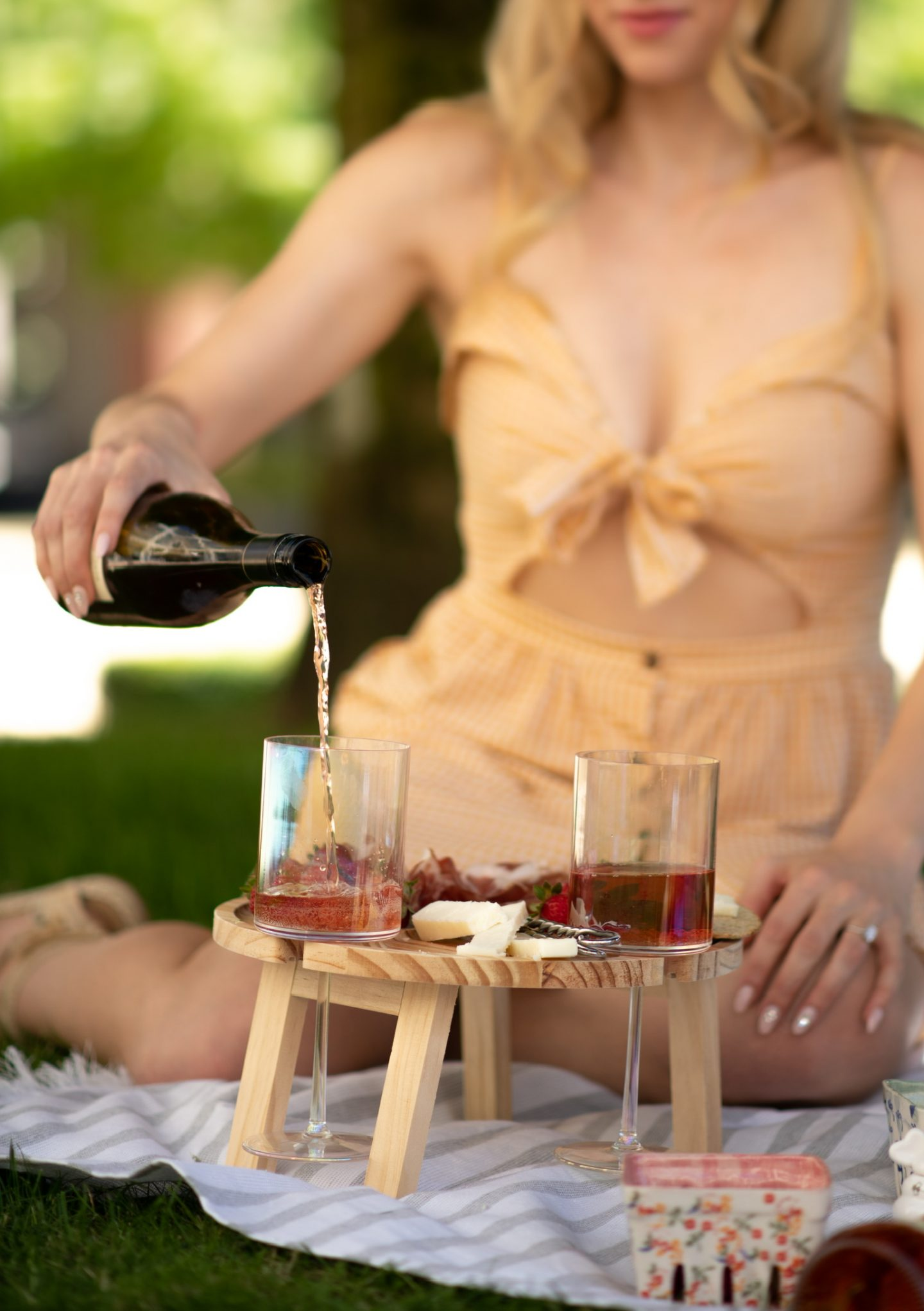 legallee blonde with foldable picnic table sharing summer picnic accessories and menu